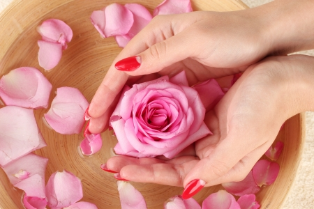 woman hands with wooden bowl of water with petals Stock Photo - 15994898