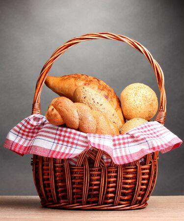 delicious bread in basket on wooden table on gray background Stock Photo - 16078170