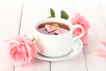 cup of tea with roses on white wooden table photo