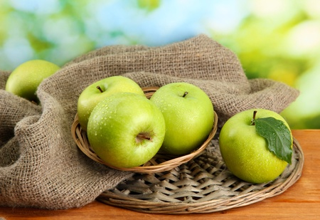 Ripe green apples in basket on burlap, on wooden table, on green background photo