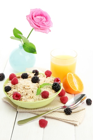 tasty oatmeal with berries and glass of juice, on white wooden table Stock Photo - 16078624