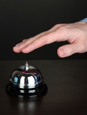 Hand ringing in service bell on wooden table on black background Stock Photo - 16078631