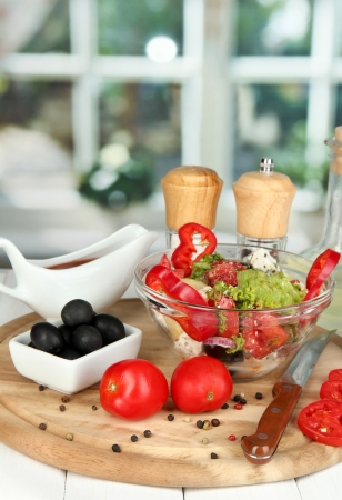 Fresh greek salad in glass bowl surrounded by ingredients for cooking on wooden table on window background Stock Photo - 16079117