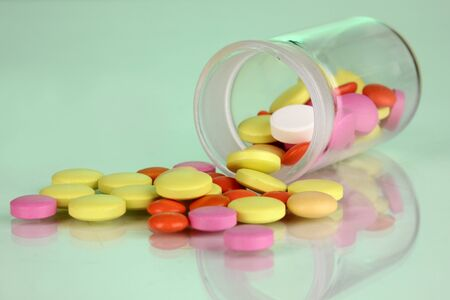 Pills in receptacle on green background photo