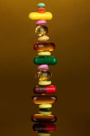 Capsules and pills on orange background photo