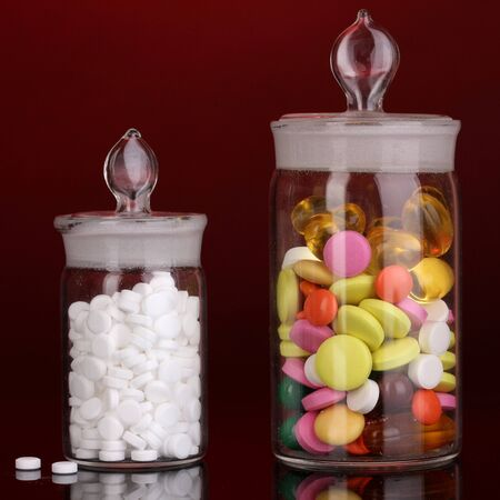Capsules and pills in receptacles on red background Stock Photo - 16078685