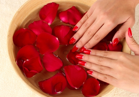 woman hands with wooden bowl of water with petals photo