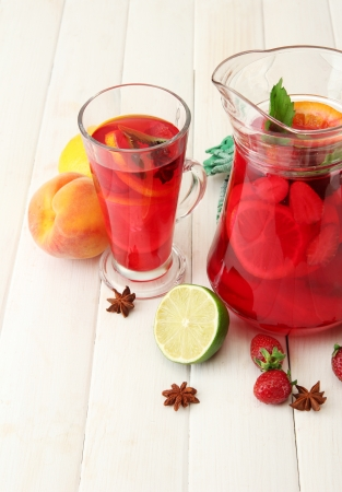 sangria in jar and glass with fruits, on white wooden table photo