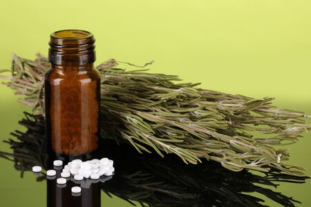 cures: bottle with pills and herbs on green background. concept of homeopathy