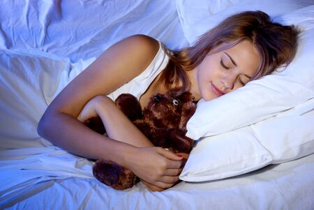 young beautiful woman with toy bear sleeping on bed in bedroom Stock Photo - 17129731
