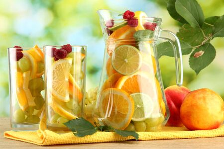 jar and glasses with citrus fruits and raspberries, on green background photo