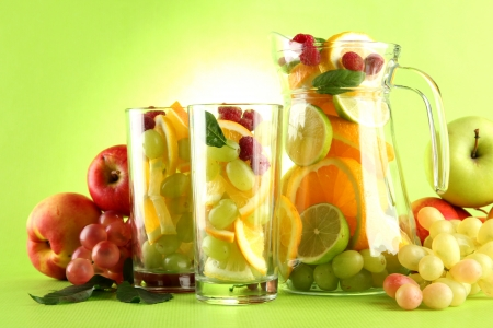 jar and glasses with citrus fruits and raspberries, on green background Stock Photo - 16106273