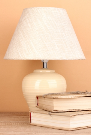 table lamp and books on beige background photo