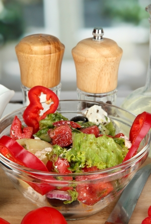Fresh greek salad in glass bowl surrounded by ingredients for cooking on wooden table on window background close-up Stock Photo - 16106453