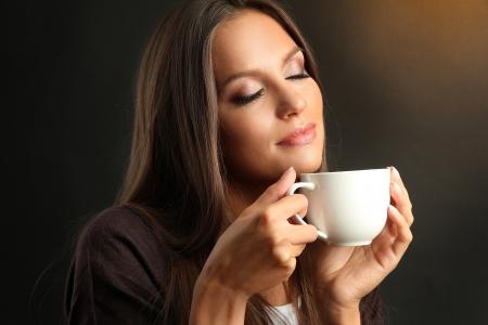 tazas de cafe: hermosa mujer joven con la taza de café, sobre fondo marrón