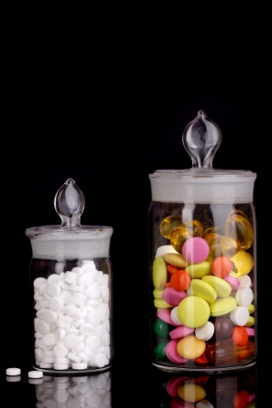 Capsules and pills in receptacles on purple background photo