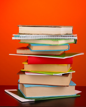 Stack of interesting books and magazines on wooden table on red background photo