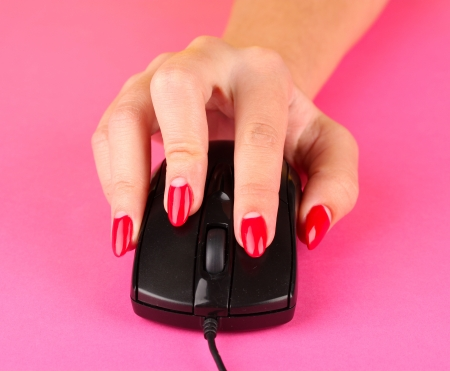 Closeup of female fingers and nails on computer mouse on color background photo