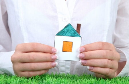 concept: woman hands with paper house, close up photo