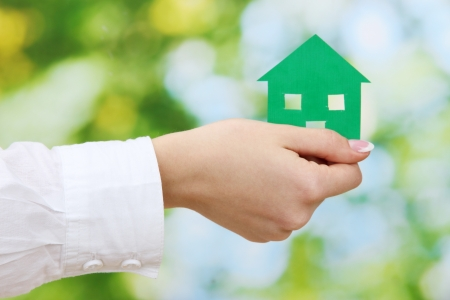 concept: woman hand with paper house on green background, close up Stock Photo - 16106280