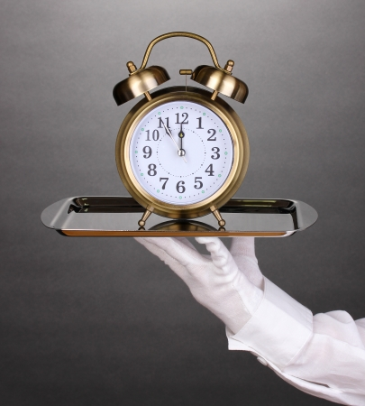 Hand in glove holding silver tray with alarm clock on grey background photo