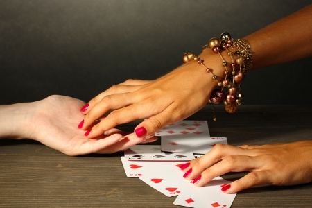 palmist: reading the lines hand and womans hands on grey backcground