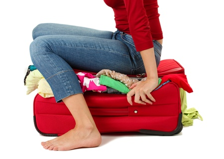 luggage pieces: The girl is trying to close suitcase crammed on white background Stock Photo