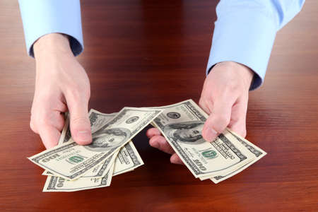 man recounts dollars on a wooden table close-up Stock Photo - 16107063