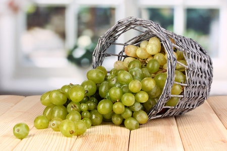 Ripe green grapes in basket on wooden table on window background