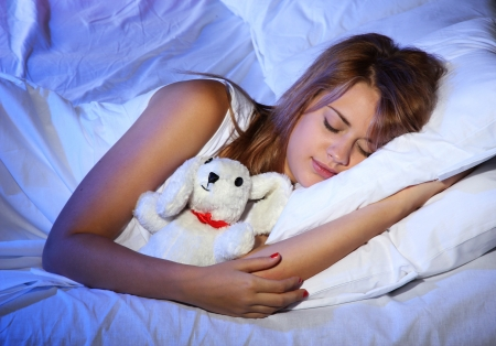 young beautiful woman with toy rabbit sleeping on bed in bedroom Stock Photo - 17129732
