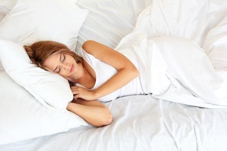 mujer en la cama: joven y bella mujer durmiendo en la cama en el dormitorio Foto de archivo