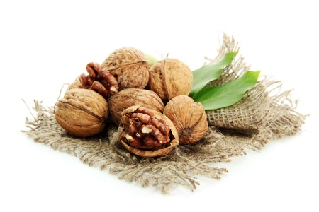 heap up: walnuts with green leaves on burlap, isolated on white