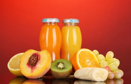 Delicious multifruit juice in a bottle and fruit next to it on red background photo
