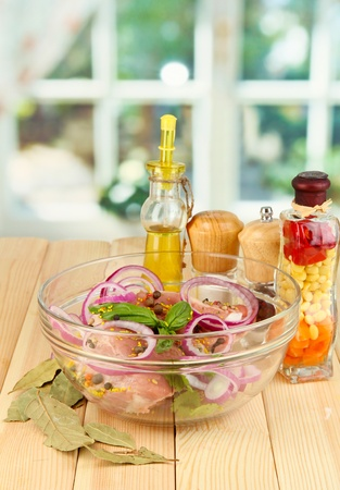 A large piece of pork marinated in bowl with herbs, spices and cooking oil on wooden table on window background Stock Photo - 16106963