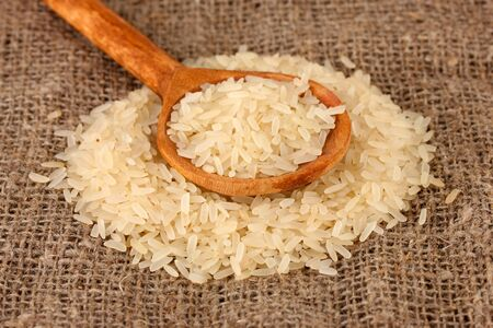 rice on sacking  in wooden  spoon Stock Photo - 16107138
