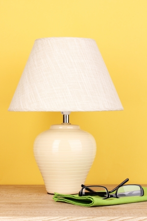 table lamp and glasses on yellow background photo