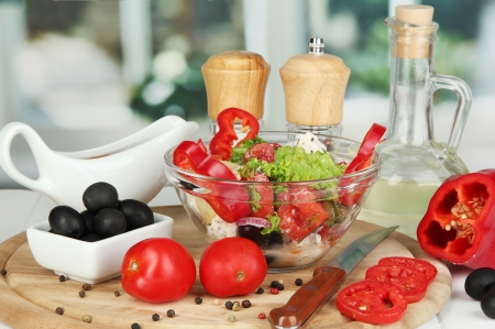 Fresh greek salad in glass bowl surrounded by ingredients for cooking on wooden table on window background Stock Photo - 16107024