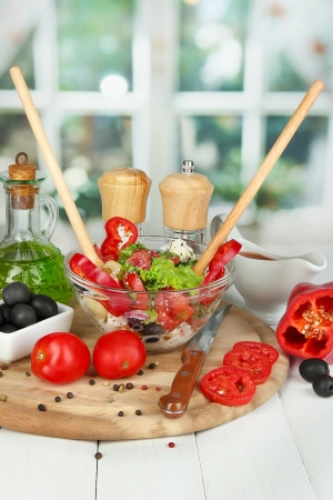 Fresh greek salad in glass bowl surrounded by ingredients for cooking on wooden table on window background Stock Photo - 16107136