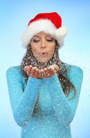 beautiful young woman blowing snow, on blue background photo