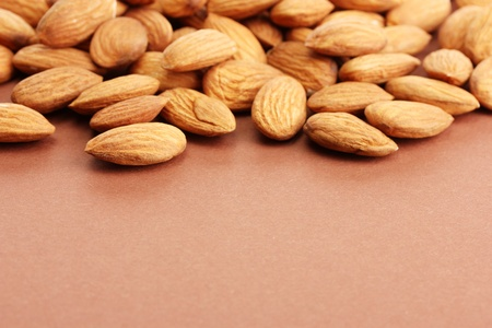 tasty almond nuts, on brown background photo