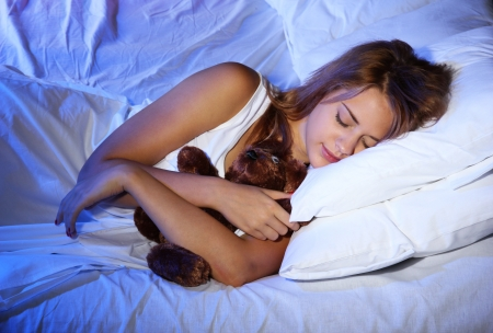 young beautiful woman with toy bear sleeping on bed in bedroom Stock Photo - 17129735