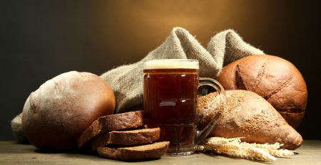 tankard of kvass and rye breads with ears, on wooden table on brown background Stock Photo - 16191373
