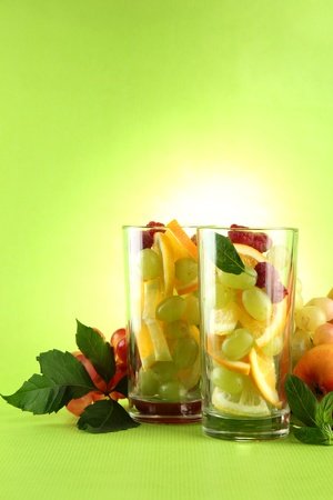 transparent glasses with citrus fruits, on grren background Stock Photo - 16191366
