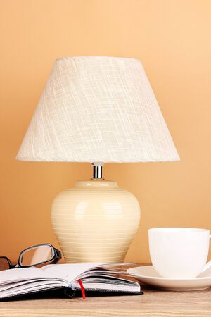 table lamp with cup and glasses on beige background photo