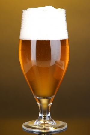 Glass of beer on yellow background photo