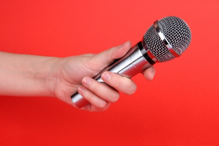 electronic voting: Silver microphone in hand on red background Stock Photo