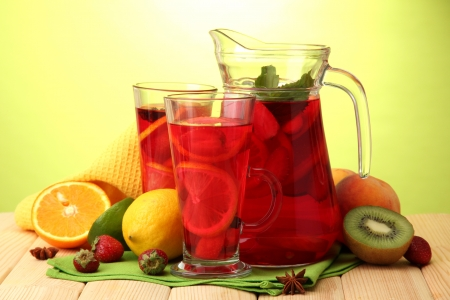 sangria in jar and glasses with fruits, on wooden table, on green background photo