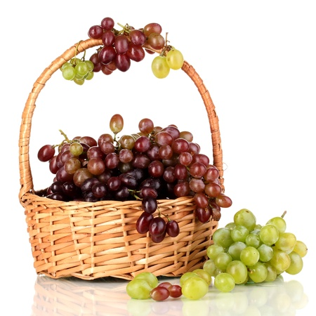 Delicious ripe pink and green grapes in basket isolated on white photo