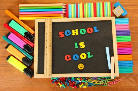 Small chalkboard with school supplies on wooden background. Back to School Stock Photo - 16195358