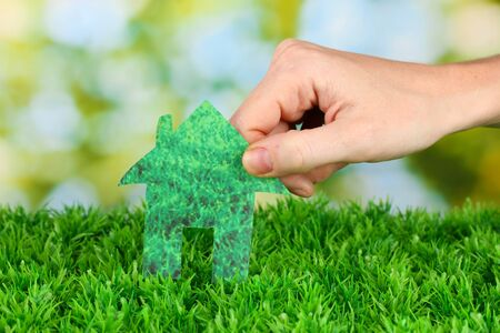 Female hand holding paper house on green background, close up Stock Photo - 16195281